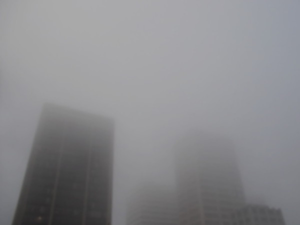A city's familiar skyscrapers are swallowed by morning fog.